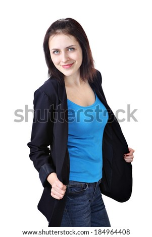 Vertical portrait of one young smiling caucasian woman, 18 years old, dressed in a dark blue office jacket, light blue tank top and jeans trousers, isolated on white background. - stock photo