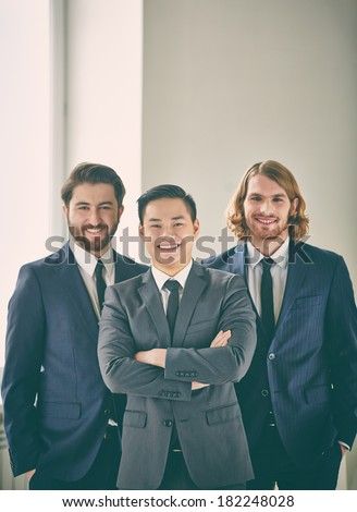 Vertical portrait of successful business partners smiling and looking at camera  - stock photo
