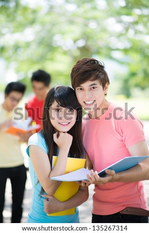 Vertical portrait of two students posing for the camera with notepads on the foreground - stock photo