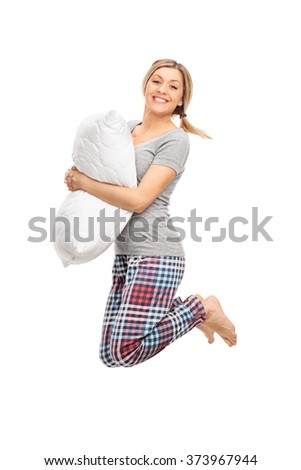 Vertical profile shot of a blond woman holding a pillow and jumping isolated on white background - stock photo