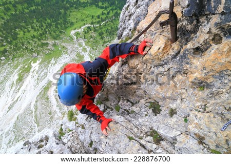 "Vertical rock wall of via ferrata ""Meisules"" and woman climber high above ground, Sella massif, Dolomite Alps, Italy - stock photo"