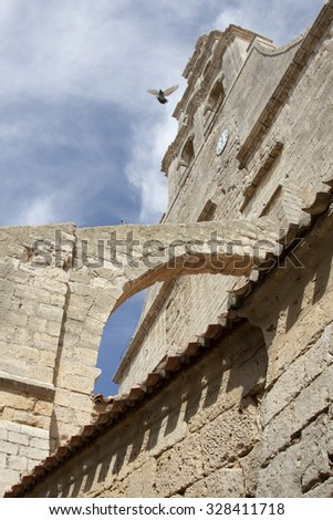 vertical romanesque church tower with buttress and dove  - stock photo
