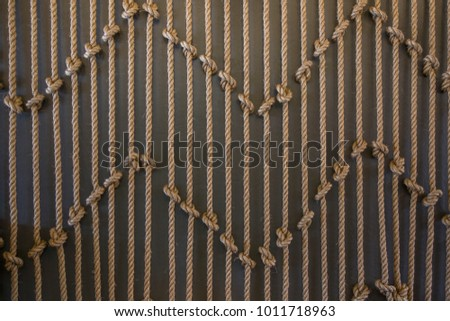 Vertical ropes with a lot of knots in front of Brown background