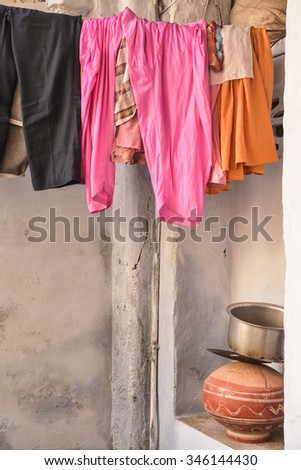 Vertical, selective focus of clothing hanging to dry on a line and various pots for brewing tea. This was shot outside a home in Udaipur, Rajasthan, India.  - stock photo