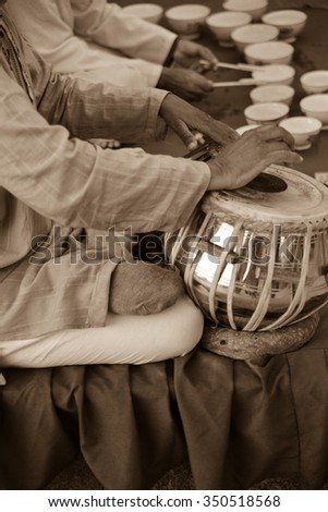 Vertical, selective focus, sepia toned shot of two men playing music at Jag Mandir Palace. One man is playing cups and the other is playing a drum. This was shot in Udaipur, India on Lake Pichola.  - stock photo