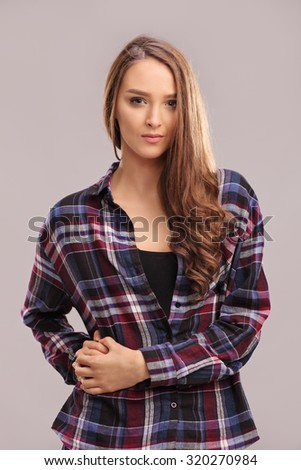 Vertical shot of a beautiful brunette woman in a casual checkered shirt posing against a gray background - stock photo