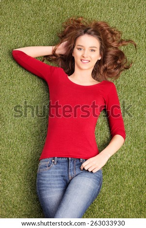Vertical shot of a beautiful carefree woman lying in a field on the grass - stock photo
