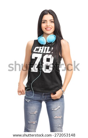Vertical shot of a beautiful young woman in a hip hop outfit posing with blue headphones around her neck isolated on white background - stock photo