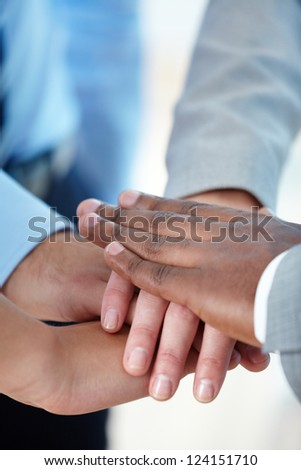 Vertical shot of a business group putting hands together to express their team spirit - stock photo