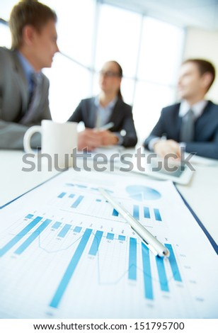 Vertical shot of a business team being on a meeting, focus on financial report in the foreground