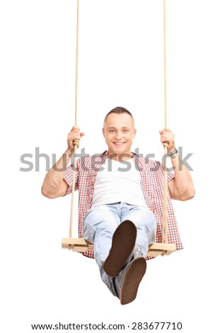 Vertical shot of a carefree young man swinging on a wooden swing and looking at the camera isolated on white background - stock photo