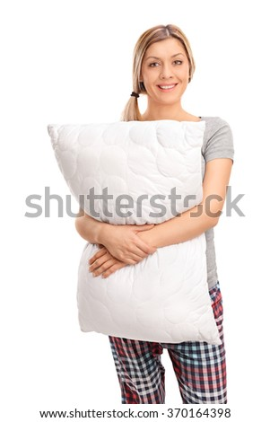 Vertical shot of a cheerful blond woman hugging a pillow and looking at the camera isolated on white background - stock photo