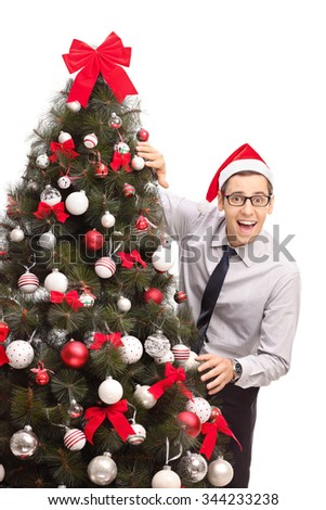 Vertical shot of a cheerful guy with Santa hat standing next to a Christmas tree and looking at the camera isolated on white background - stock photo