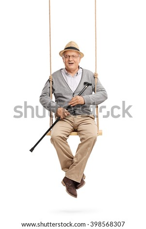 Vertical shot of a cheerful senior holding a cane and sitting on a wooden swing isolated on white background