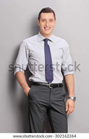 Vertical shot of a cheerful young businessman posing against a gray background
