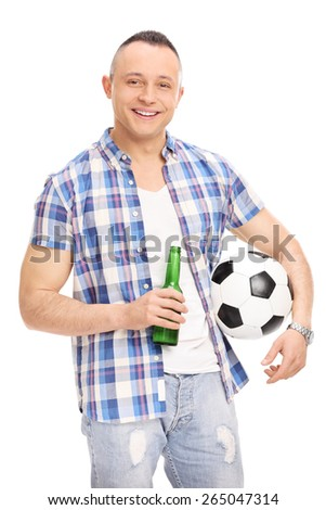Vertical shot of a cheerful young guy holding a bottle of beer and a football isolated on white background - stock photo