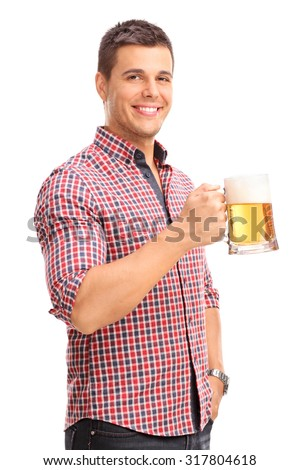 Vertical shot of a cheerful young man holding a beer mug full of beer and smiling isolated on white background
