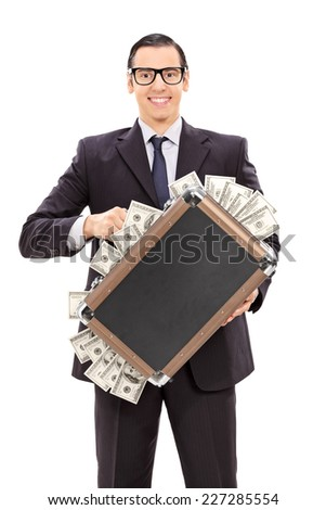Vertical shot of a delighted businessman holding a briefcase full of money isolated on white background - stock photo