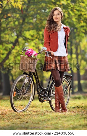 Vertical shot of a fashionable woman posing with her bicycle in park  - stock photo