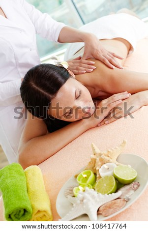 Vertical shot of a girl lying on the massage table, massage therapist doing the procedure - stock photo