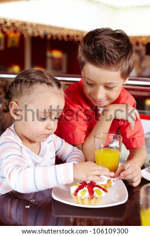 Vertical shot of a guy and his little sister eating cakes with cream together - stock photo