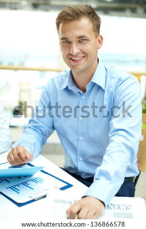 Vertical shot of a handsome businessman looking at camera with smile - stock photo