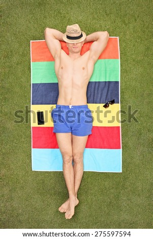 Vertical shot of a handsome young man sleeping shirtless on a towel in his backyard - stock photo