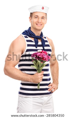 Vertical shot of a handsome young sailor holding a bouquet of pink flowers and looking at the camera isolated on white background - stock photo