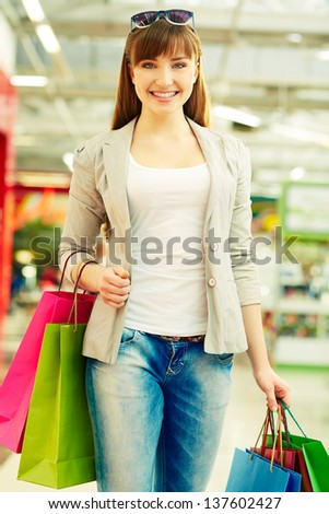 Vertical shot of a happy girl carrying her purchases after shopping