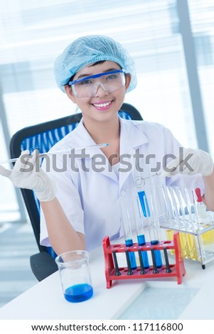 Vertical shot of a happy researcher analyzing samples at the lab - stock photo