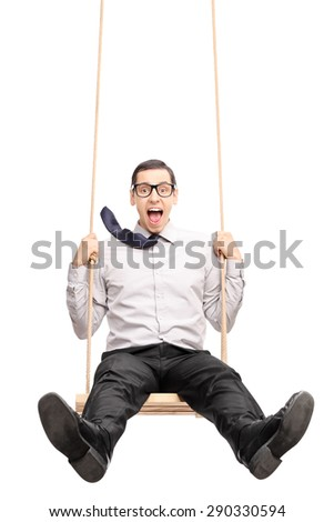 Vertical shot of a joyful young guy swinging fast on a wooden swing isolated on white background - stock photo