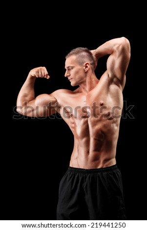 Vertical shot of a male bodybuilder showing his muscles on black background