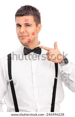 Vertical shot of a man covered in lipstick kiss marks isolated on white background - stock photo