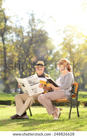 Vertical shot of a mature couple relaxing seated on a bench in park  - stock photo