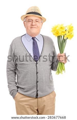 Vertical shot of a romantic senior gentleman holding a bouquet of yellow tulips and looking at the camera isolated on white background - stock photo