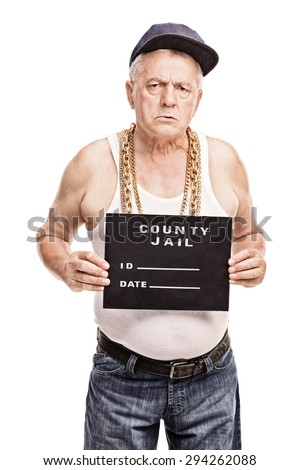 Vertical shot of a senior gangster in a hip hop outfit posing for a mug shot isolated on white background  - stock photo