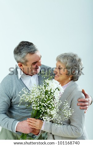 Vertical shot of a senior man giving his lady a bouquet - stock photo