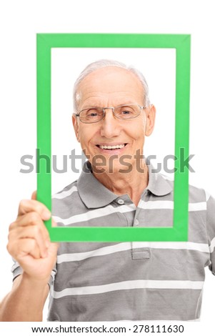 Vertical shot of a senior man holding a green picture frame in front of his face isolated on white background - stock photo
