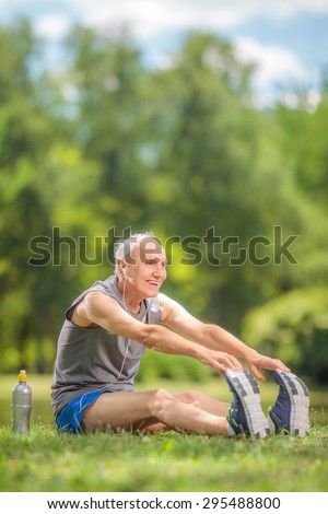 Vertical shot of a senior man stretching his legs seated by a pond in a park and listening to music on headphones - stock photo
