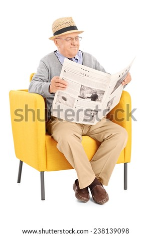 Vertical shot of a senior reading a newspaper in a modern armchair isolated on white background - stock photo