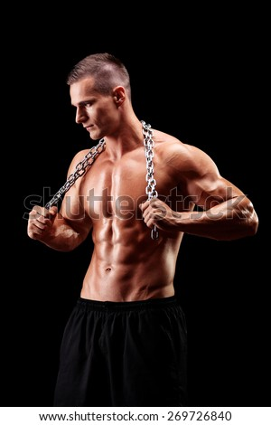 Vertical shot of a shirtless young man holding a chain around his neck on black background - stock photo