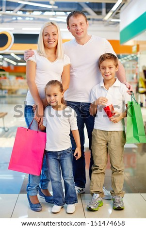 Vertical shot of a shopping family being happy with their spree weekend