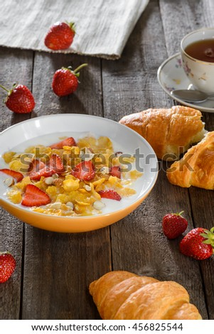 Vertical shot of a tasty breakfast on the vintage table. Delicious cereals with pieces of strawverries and milk. - stock photo