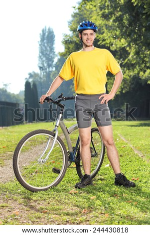 Vertical shot of a young biker posing with his bicycle in a park - stock photo
