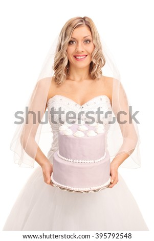 Vertical shot of a young blond bride carrying a wedding cake and looking at the camera isolated on white background