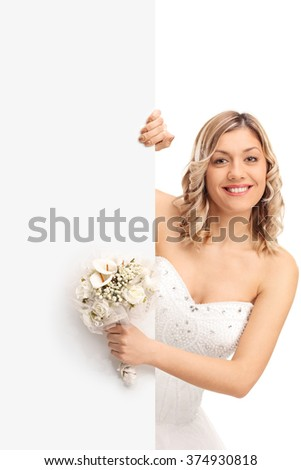 Vertical shot of a young bride holding a wedding flower and standing behind a blank panel isolated on white background - stock photo