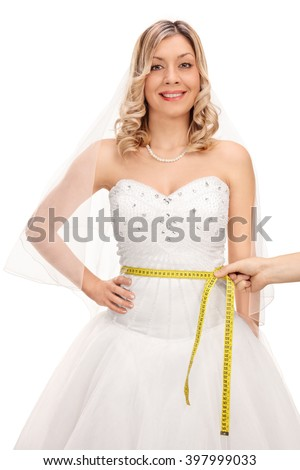 Vertical shot of a young bride posing in a wedding dress and someone measuring her waist isolated on white background