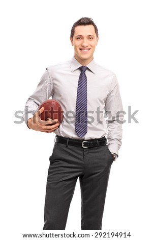 Vertical shot of a young businessman holding a football and looking at the camera isolated on white background - stock photo