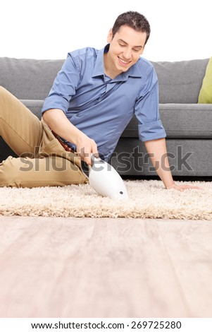 Vertical shot of a young cheerful man cleaning a carpet with a handheld vacuum cleaner in  front of a gray sofa isolated on white background - stock photo