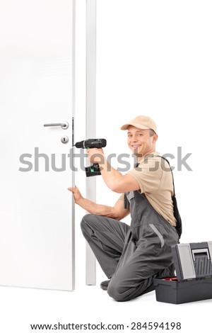 Vertical shot of a young locksmith screwing a lock on a door with a hand drill and looking at the camera isolated on white background - stock photo